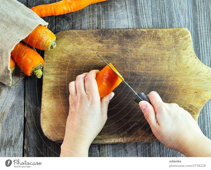 Zwei weibliche Hände mit einem Messer Frau Hand Erwachsene Essen Lebensmittel grau Körper frisch Küche Gemüse Ernte Top Salatbeilage Hälfte Möhre