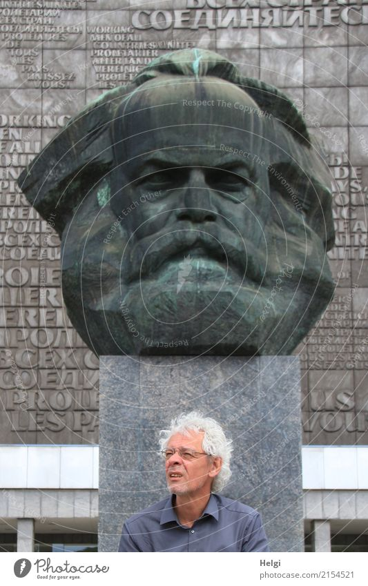 männlicher Senior mit silbergrauen Locken, Brille und Dreitagebart sitzt vor dem Karl-Marx-Denkmal in Chemitz Mensch maskulin Männlicher Senior Mann 1