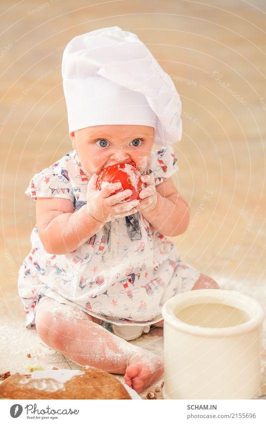Ein süßes kleines Mädchen mit Kochmütze sitzt auf dem mit Mehl verunreinigten Küchenboden, spielt mit dem Essen, macht Unordnung und hat Spaß Lifestyle Freude