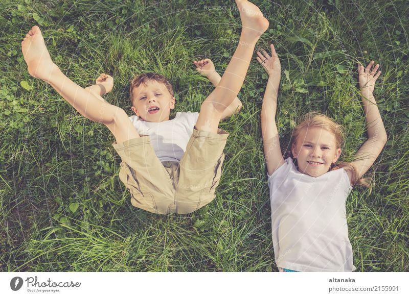 Zwei glückliche Kinder, die auf dem Gras zur Tageszeit spielen. Mensch Natur Ferien & Urlaub & Reisen Sommer schön grün Freude Gesicht Lifestyle Liebe Wiese
