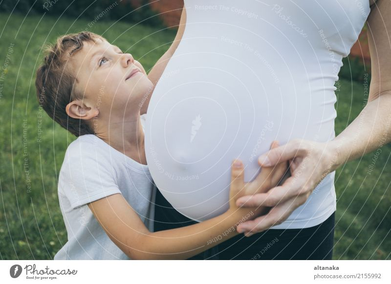 Glücklicher kleiner Junge, der Mutter im Park zur Tageszeit umarmt. Kind Frau Natur Ferien & Urlaub & Reisen Sommer Freude Erwachsene Lifestyle Liebe Sport
