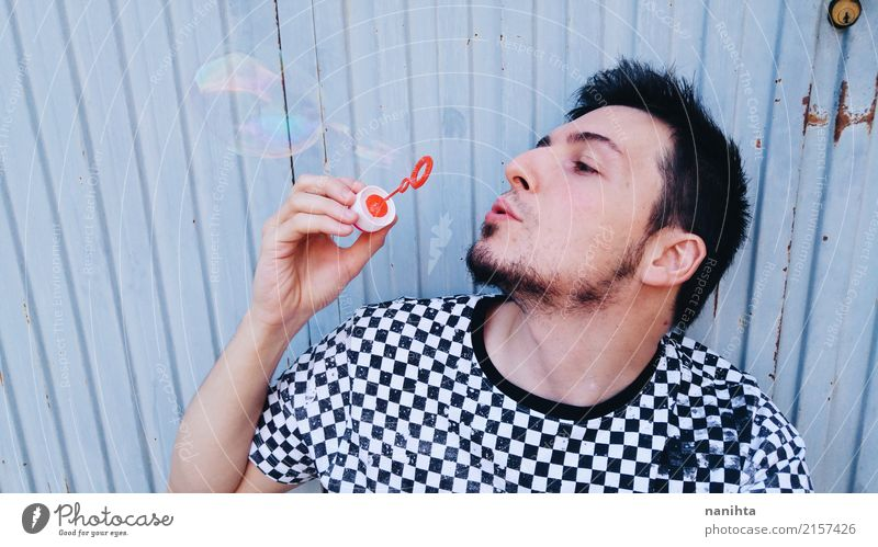 Junger Mann, der mit Seifenblasen spielt Mensch Jugendliche blau weiß Erholung 18-30 Jahre schwarz Erwachsene Lifestyle lustig Stil Spielen Haare & Frisuren