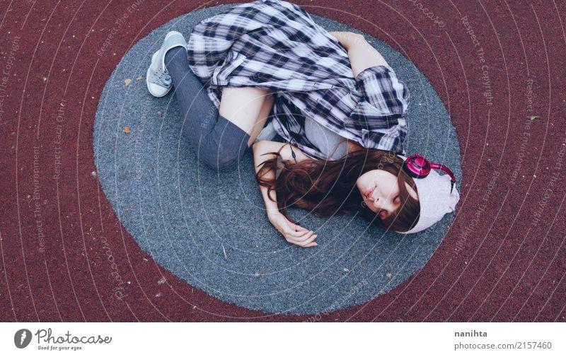 Die junge Frau, die Musik hört, liegt auf dem Boden Lifestyle Stil Erholung Mensch feminin Junge Frau Jugendliche 1 18-30 Jahre Erwachsene Musik hören Kopfhörer