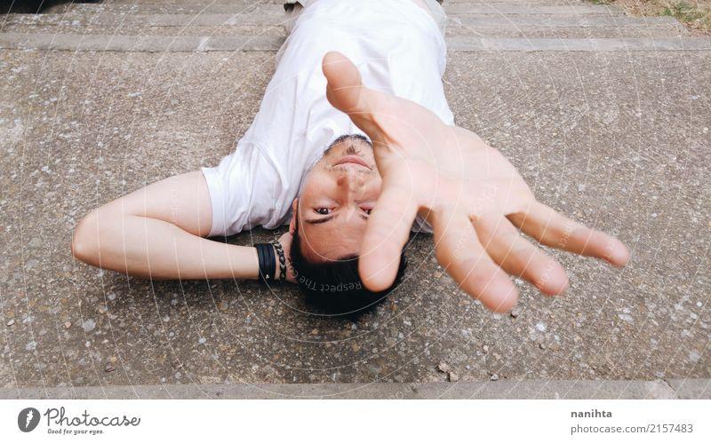 Junger Mann hob seine Hand an, um etwas zu berühren Mensch Jugendliche Stadt weiß 18-30 Jahre Erwachsene Lifestyle Stil grau maskulin liegen Erfolg Lächeln