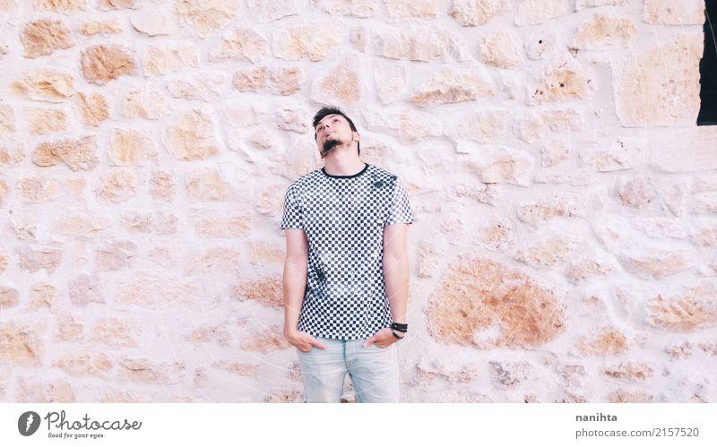 Junger Mann, der mit einer Steinwand als Hintergrund aufwirft Lifestyle Stil Mensch maskulin Jugendliche 1 18-30 Jahre Erwachsene Jugendkultur Bekleidung