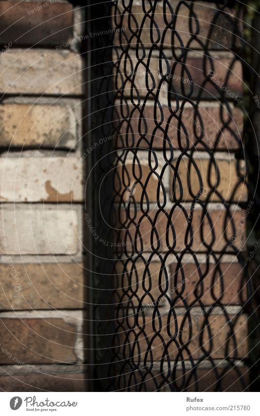 BefestigungsWall Mauer Wand Zaun Zaunpfahl Stein Metall bedrohlich dunkel stachelig trist braun gelb schwarz Sicherheit Schutz Feindseligkeit Farbfoto