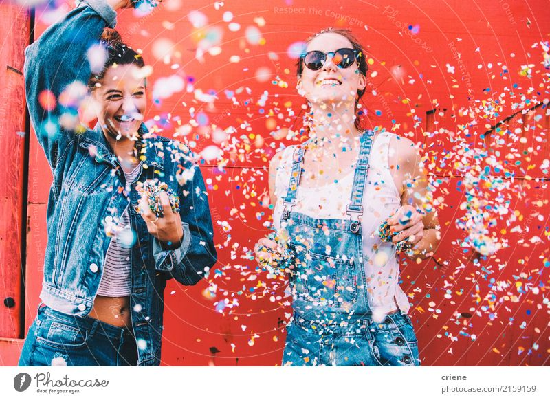 Zwei glückliche junge erwachsene Freunde, die Konfettis tanzen und werfen Lifestyle Freude feminin Junge Frau Jugendliche 2 Mensch 18-30 Jahre Erwachsene