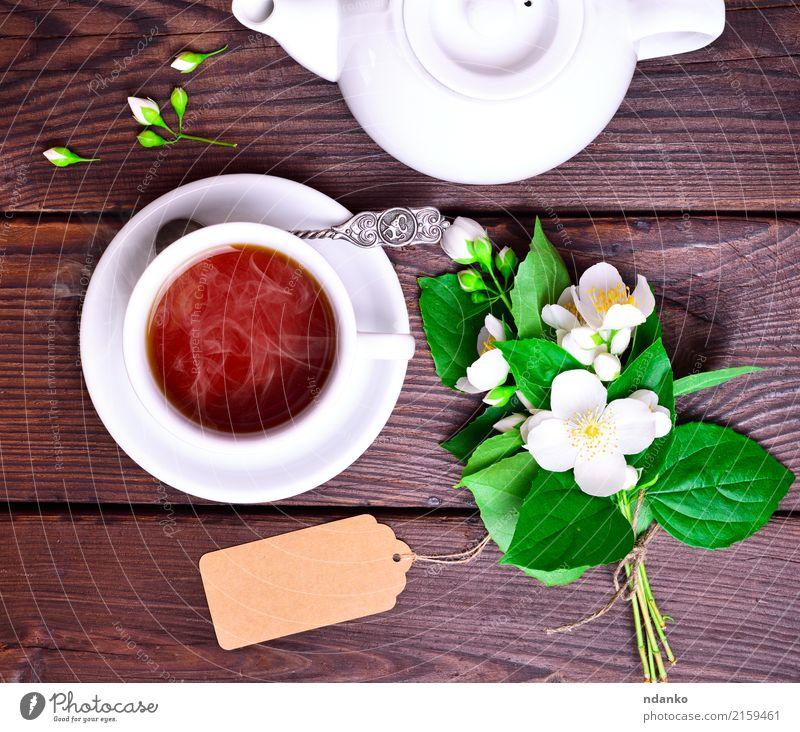 heißer schwarzer Tee in einer weißen Tasse Frühstück Getränk Löffel Tisch Blume Blatt Holz frisch oben retro braun grün Tradition Jasmin trinken Lebensmittel