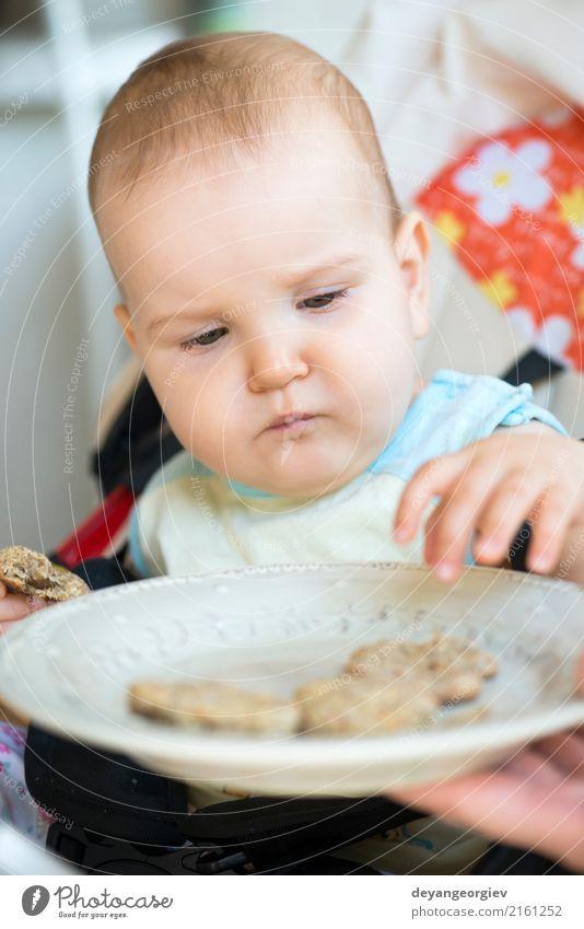 Baby isst alleine. Essen Frühstück Mittagessen Löffel Stuhl Tisch Kind Kleinkind klein niedlich Appetit & Hunger Einsamkeit Kekse Speise Lebensmittel Mädchen