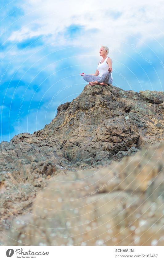 Schöne reife gealterte Frau sitzt auf eine Klippe, die Yoga tut Mensch Himmel Natur blau Sommer schön Landschaft Erholung Wolken ruhig Freude Ferne Strand