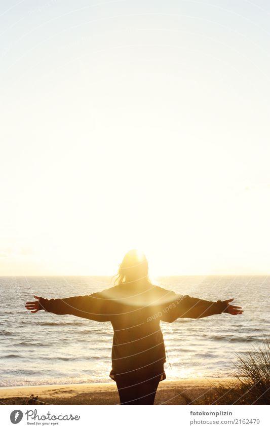 Frau mit ausgestreckten Armen vor leuchtendem Sonnenuntergang am Meer Ferne Freiheit Gleichgewicht Spiritualität Sonnenenergie mental Sonnenaufgang mystisch