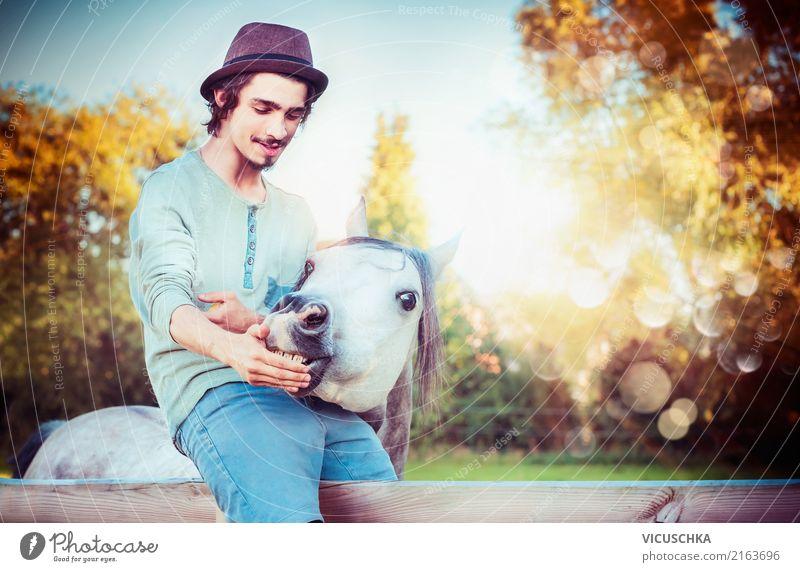 Junger Mann sitzt auf dem Zaun und füttert Pferd Lifestyle Stil Mensch Jugendliche 1 Natur Tier Gefühle Stimmung young Tierliebe Freundschaft Farbfoto