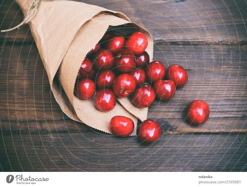 rote Kirsche in einer Papiertüte Frucht Dessert Essen Vegetarische Ernährung Saft Sommer Garten Tisch Holz frisch natürlich retro saftig braun Hintergrund