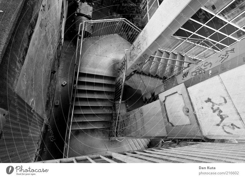 Backstreet Graffiti dreckig Architektur Beton Treppe authentisch Etage Bauwerk tief Geländer Säule Vogelperspektive Schwarzweißfoto abwärts Treppengeländer