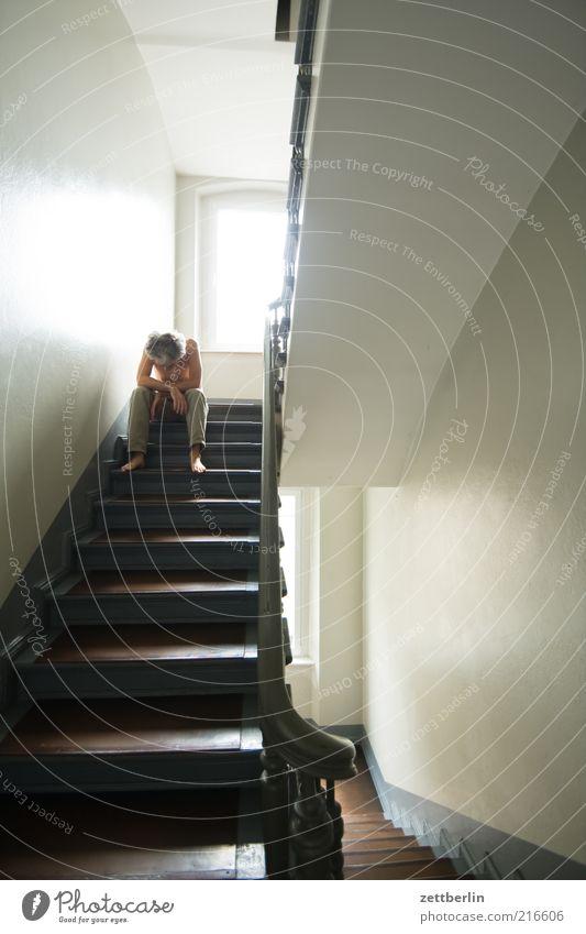 Treppenhaus maskulin Mann Erwachsene 1 Mensch Haus Mauer Wand sitzen warten Traurigkeit Sorge Trauer Einsamkeit Geländer Fenster erleuchten Treppenabsatz