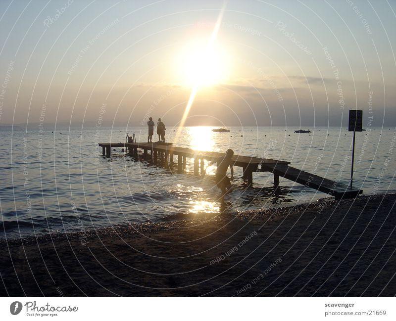 Sonnenuntergang Gardasee Sonnenstrahlen weiß Licht Abendsonne Sonnenaufgang dunkel See Wellen Wasserfahrzeug Strand Steg Horizont Holz Romantik Beleuchtung blau