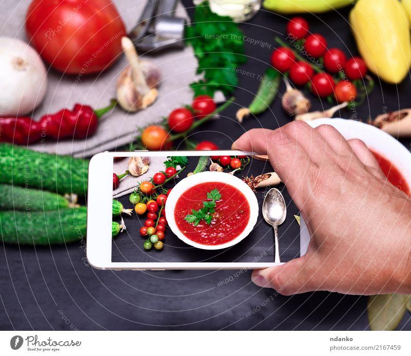 Smartphone in der menschlichen Hand Gemüse Suppe Eintopf Ernährung Mittagessen Abendessen Vegetarische Ernährung Diät Teller Löffel Tisch Küche PDA Holz frisch