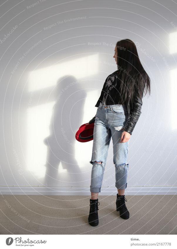 Nastya Raum feminin Frau Erwachsene 1 Mensch Mauer Wand Jeanshose Jacke Schuhe Hut schwarzhaarig langhaarig beobachten drehen festhalten Blick schön