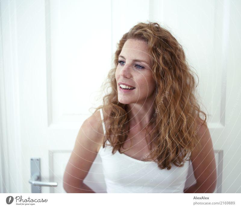 junge, rothaarige Frau steht vor einer weißen Tür und lächelt elegant Stil Glück schön Gesicht Wellness Leben Raum Junge Frau Jugendliche Sommersprossen