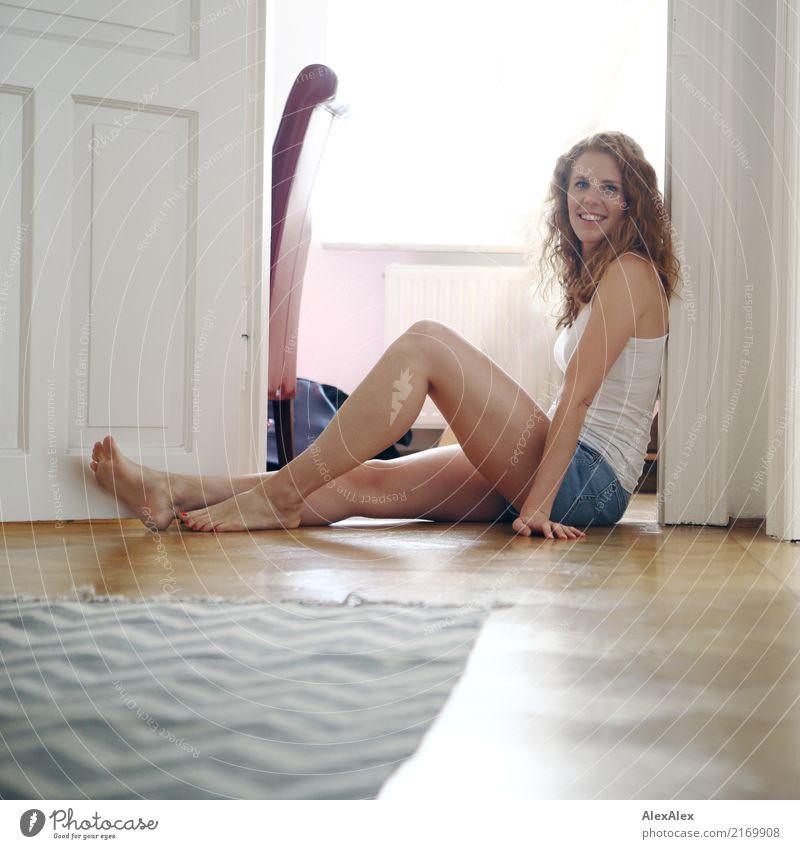 Portrait einer jungen, rothaarigen, sportlichen Frau in Hotpants, die im Flur am Boden sitzt und lächelt Stil Glück schön harmonisch Wohlgefühl Wohnung Raum Tür