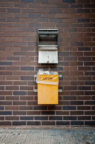 englischer Mülleimer an einer Wand Stadt gelb Umwelt dreckig Fußweg Stadtzentrum Backstein Umweltschutz England minimalistisch Englisch Müllbehälter Müllmann