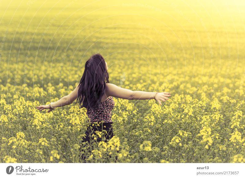 Schöne junge Frau im Frühling oder Sommer auf der Wiese geniesst die Sonne. Das hübsche Mädchen steht in einem weiten Feld voller Raps in der Natur. Symbolisiert Glück, Gesundheit in Balance und Freiheit voller Lebensfreude gegen Burnout und Stress.