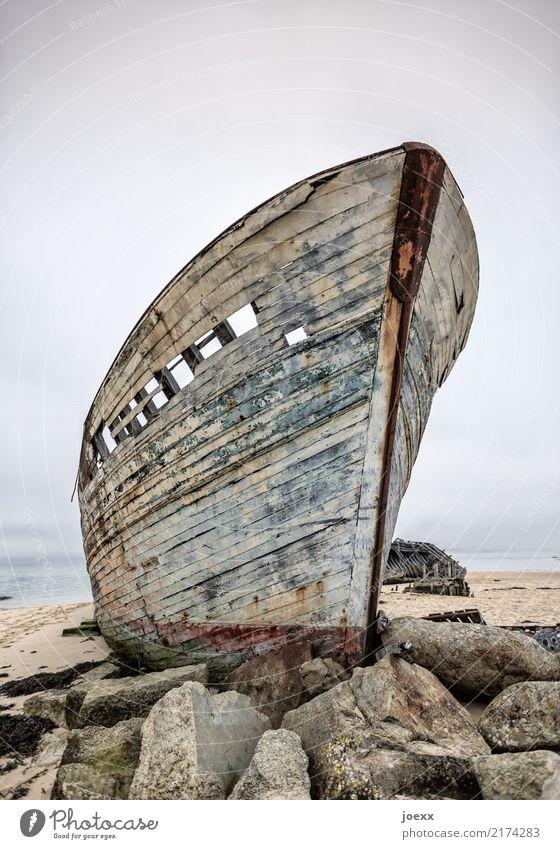 Aus der Zeit Horizont Felsen Fischerboot Holz alt hoch maritim blau braun Einsamkeit Idylle Tod Zerstörung Schiffswrack Bootswrack verrotten Farbfoto