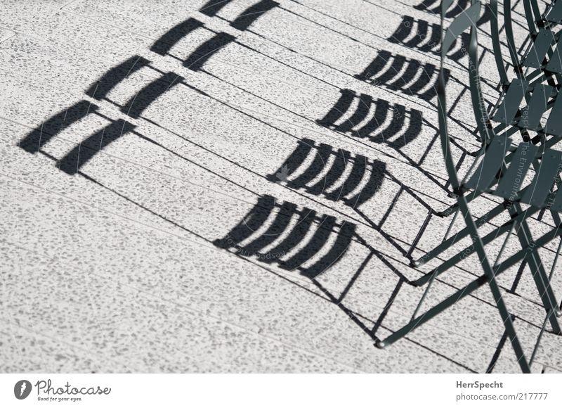 Noch Schattenplätze frei grün grau Metall Beton Stuhl Schattenspiel Textfreiraum links Klappstuhl