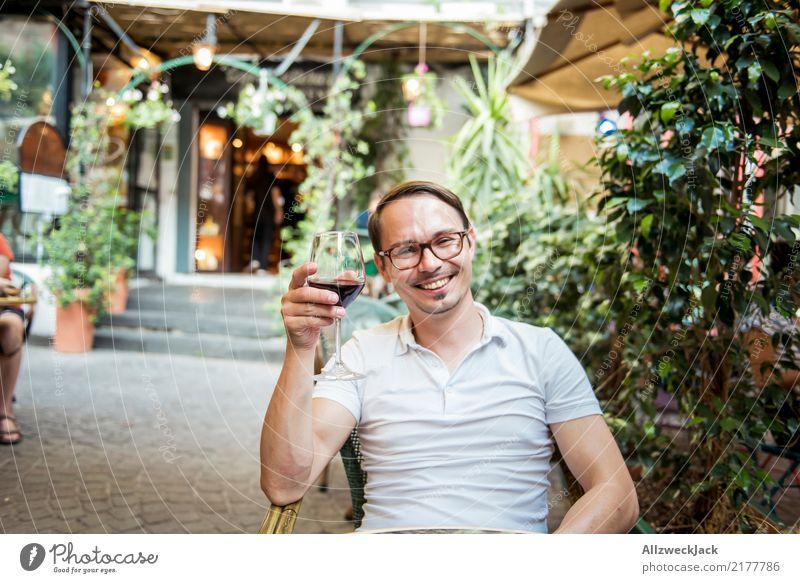 Mann mit Weinglas sitzt im Stuhl und freut sich 1 Mensch Junger Mann sitzen Tag Außenaufnahme Wärme Sommer Rotwein Alkohol trinken Zuprosten Restaurant Terrasse