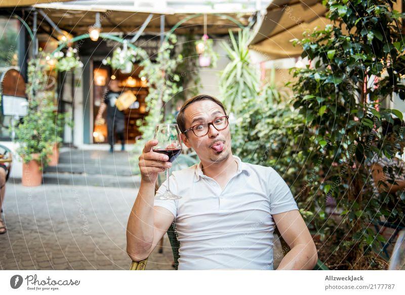 Mann mit Weinglas steckt die Zunge raus 1 Mensch Junger Mann sitzen Tag Außenaufnahme Wärme Sommer Rotwein Alkohol trinken Zuprosten Restaurant Terrasse Freude