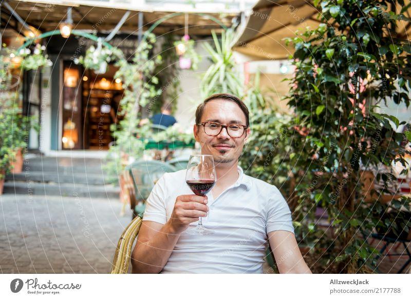 Mann mit Weinglas sitzt im Stuhl und ist zufrieden 1 Mensch Junger Mann sitzen Tag Außenaufnahme Wärme Sommer Rotwein Alkohol trinken Zuprosten Restaurant