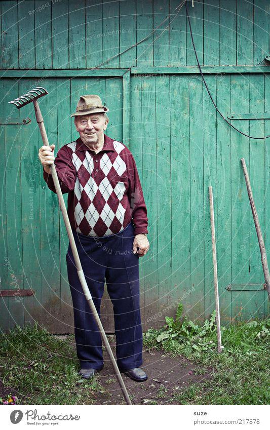Innerlich tobt er Freizeit & Hobby Garten Gartenarbeit Mensch maskulin Männlicher Senior Mann Großvater 1 Hose Hut alt Freundlichkeit grün Gärtner Wand Rechen