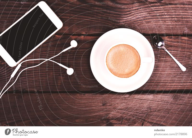 weiße Tasse mit Kaffee und Schaum Frühstück Getränk Espresso Tisch Restaurant Telefon PDA Bildschirm Holz heiß natürlich braun schwarz Farbe Cappuccino