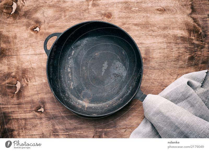 Runde schwarze Gusseisenpfanne Pfanne Tisch Küche Holz Metall Stahl alt grau braten leer Lebensmittel Hintergrund Gerät Utensil Aussicht Essen zubereiten