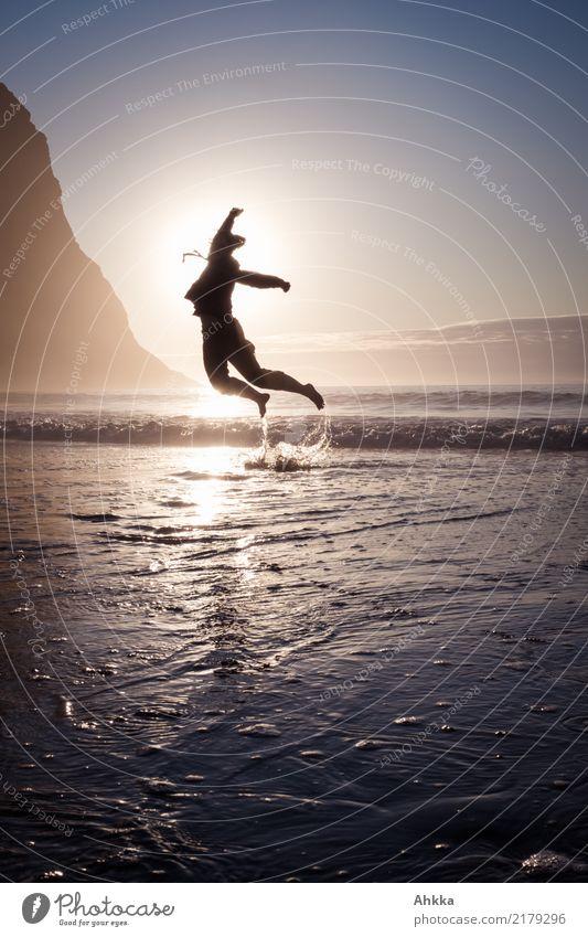 Junge Frau springt aus dem Meer in den Sonnenuntergang Leben harmonisch Zufriedenheit Sinnesorgane Abenteuer Tanzen Jugendliche Natur Wolkenloser Himmel