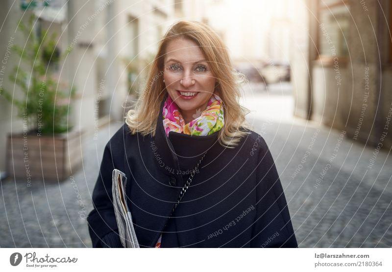 Blonde reife lächelnde Frau auf Straße elegant Glück Gesicht Business Erwachsene 1 Mensch 30-45 Jahre Zeitung Zeitschrift Fußgänger Mantel blond Lächeln