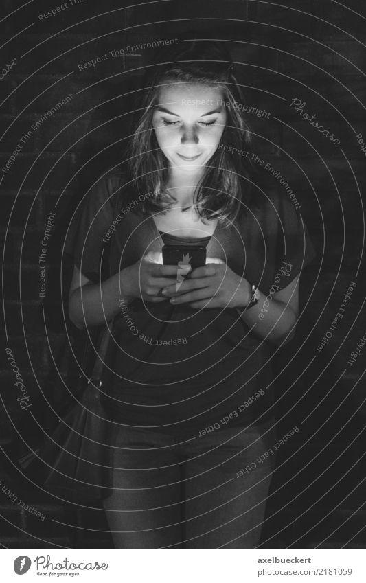 junge Frau nur vom Smartphone Display beleuchtet Lifestyle Freizeit & Hobby Telefon Handy PDA Technik & Technologie Unterhaltungselektronik Telekommunikation