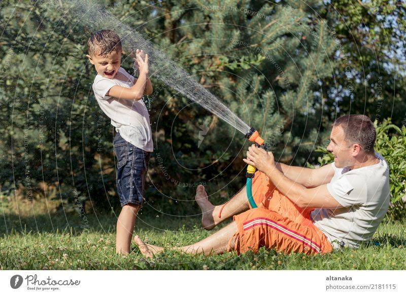 Glücklicher Vater und Sohn spielen im Garten zur Tageszeit. Menschen, die Spaß im Freien haben. Konzept der glücklichen Familie. Lifestyle Freude