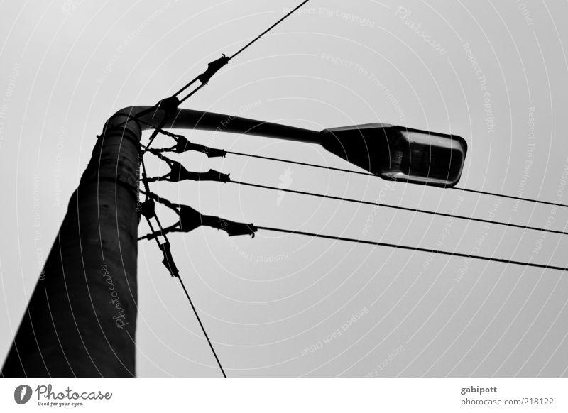 laterne laterne Laternenpfahl Lampe Straßenbeleuchtung Kabel Stahlkabel alt schwarz weiß Fortschritt Licht dunkel trüb Schwarzweißfoto Außenaufnahme Tag