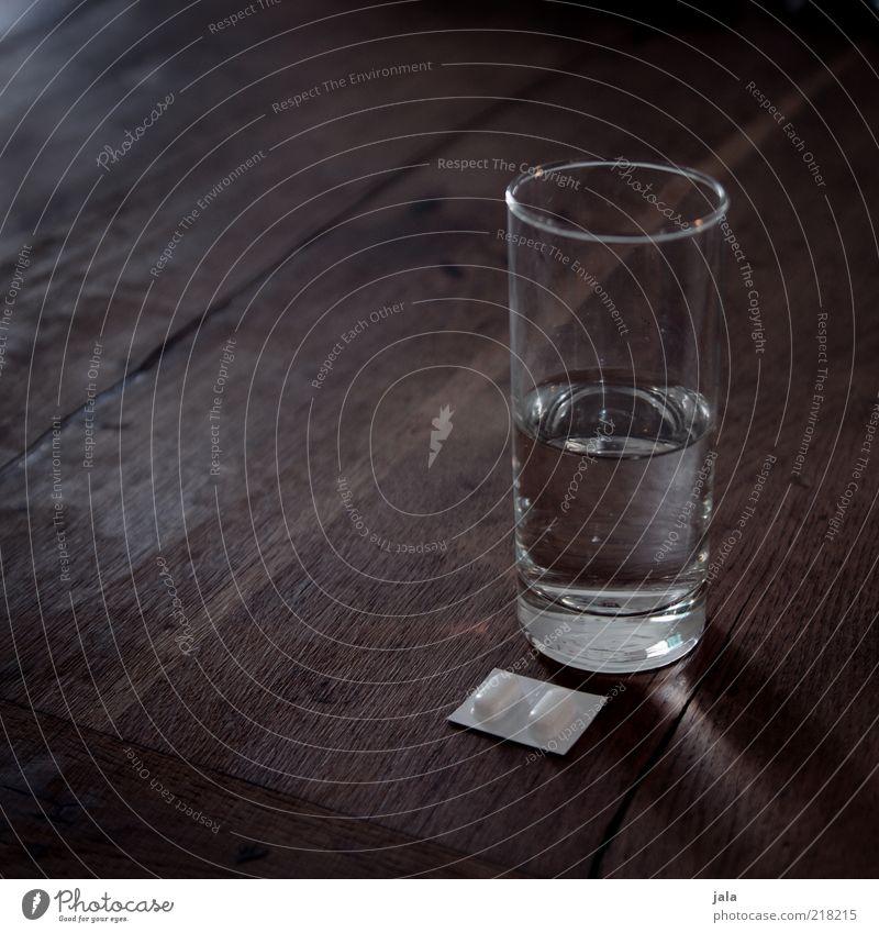 schmerz, laß nach! Getränk Trinkwasser Glas Tisch Holz Schmerz Tablette Wasser Farbfoto Gedeckte Farben Innenaufnahme Menschenleer Textfreiraum links
