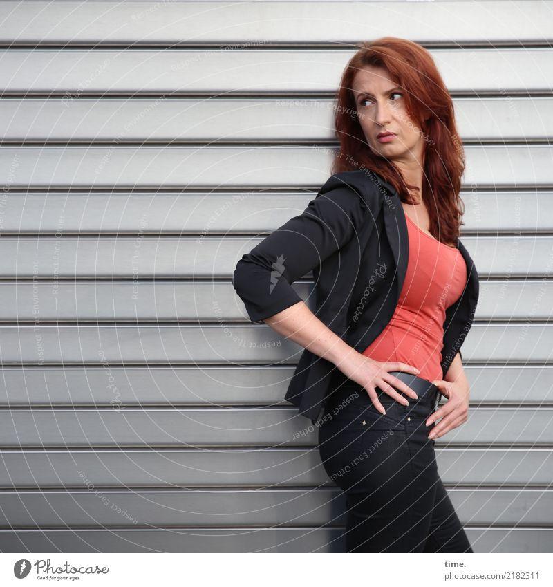 . feminin Frau Erwachsene 1 Mensch Mauer Wand Rolltor T-Shirt Hose Jacke rothaarig langhaarig Metall beobachten Denken festhalten Blick stehen ästhetisch