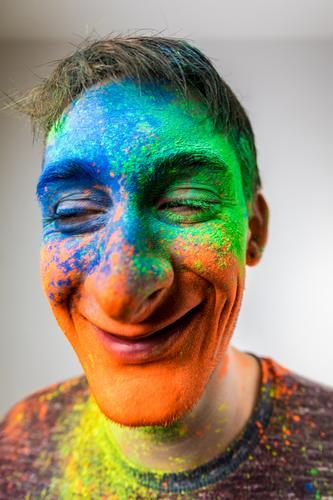 Mann mit Holi Pulver im Gesicht karikatur mehrfarbig lachen Lächeln verrückt Perspektive Holi Kino Junger Mann blau gelb grün orange Nase groß