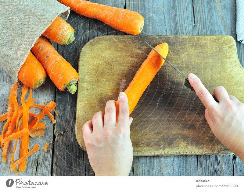 Prozess des Schneidens von frischen Karotten Gemüse Ernährung Vegetarische Ernährung Diät Saft Messer Körper Tisch Arme Hand Natur Holz natürlich Möhre