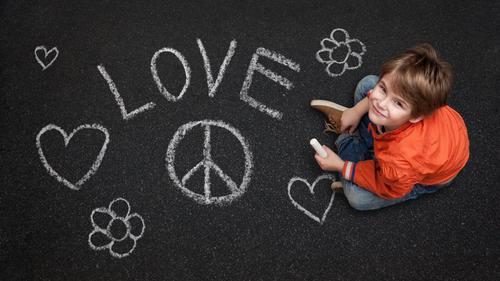 Junge mit Kreide will Frieden und Liebe Kind Mensch Straße Leben lachen Glück grau orange maskulin Kindheit Lächeln Fröhlichkeit Hoffnung Asphalt