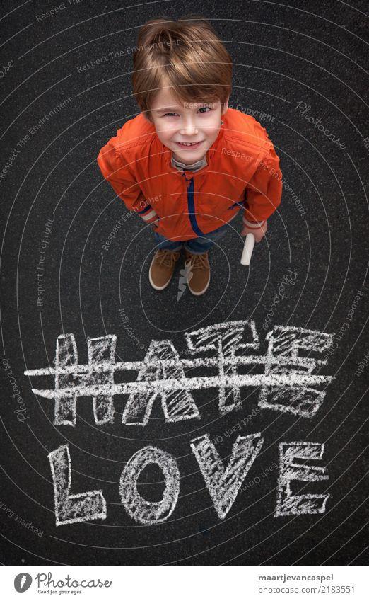Junge mit Kreide will Kein Hass sonder Liebe Mensch maskulin Kind Kindheit Leben 1 3-8 Jahre Straße Jeanshose Kreidezeichnung Lächeln schreiben stehen