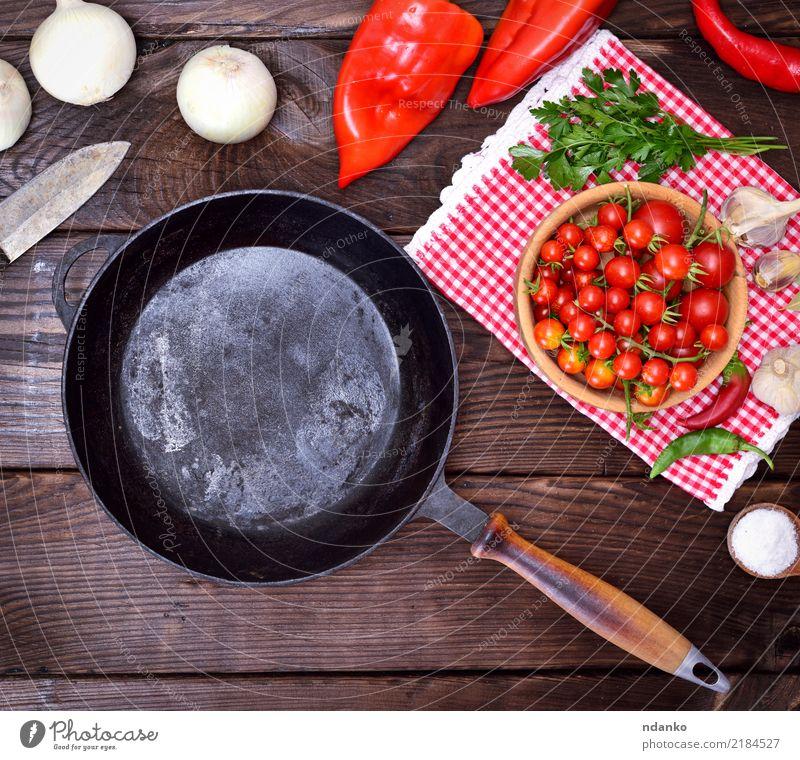 leere schwarze Gusseisenbratpfanne Lebensmittel Gemüse Ernährung Essen Pfanne Messer Küche Holz braun rot Bratpfanne rund Gußeisen Tomate Zwiebel Salz reif Koch