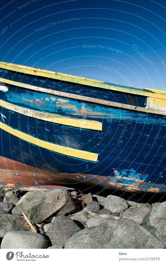 Schiffbruch alt Himmel blau gelb Holz Stein Wasserfahrzeug Küste Felsen authentisch kaputt Wandel & Veränderung verfallen Verfall Schifffahrt Schönes Wetter