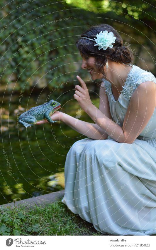 ... einen Frosch küssen ?          - junge brünette Frau im Abendkleid schaut einen Frosch an, den sie in der Hand hält feminin Junge Frau Prinzessin