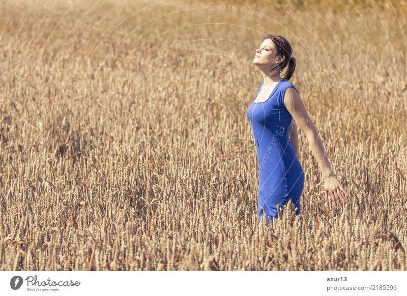 Junge Frau mit blauem Kleid genießt Herbst Sonne im Kornfeld Lifestyle schön Körper Gesundheit Wellness Leben harmonisch Wohlgefühl Zufriedenheit Sinnesorgane
