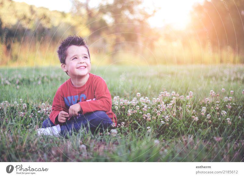 lächelndes Kind, das auf dem Gebiet sitzt Mensch Natur Ferien & Urlaub & Reisen Sommer Blume Lifestyle Frühling lustig Gefühle Wiese lachen Garten Freiheit